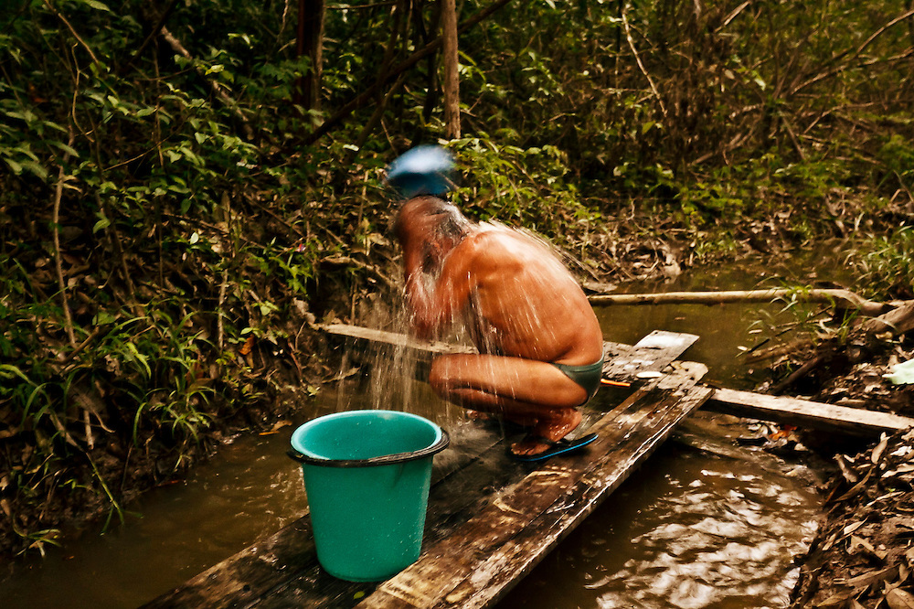 Colombia, Mocagua, 2010. Ba&ntilde;o de tarde. <br /> Una descarga de agua es el ritual para terminar el d&iacute;a. Tras la dura jornada laboral en la agricultura, este hombre se prepara para regresar a casa. Como en la pesca, el riego, el lavado y el transporte, el agua es principio y fin en el Amazonas. <br /> Afternoon bath. <br /> A showerwash is the ritual to finish the day. After the hard labour of the day farming, this man prepares to return home.  As with fishing, irrigation, washing and transport, the water is the beginning and the end in the Amazon.