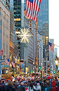 The Snowflake suspended over Fifth Avenue at 57th Street and shoppers along Fifth Avenue during Christmas season, New York City.