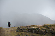 An elderly Aymara man walks into the clouds in the Bolivian Andes near the town of Sorata.