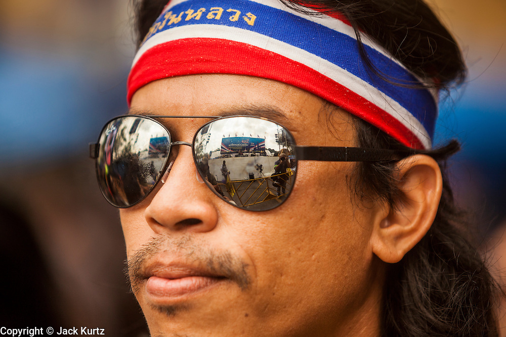 17 FEBRUARY 2014 - BANGKOK, THAILAND: The stage at Government House is reflected in the sunglasses of an anti-government protestor. The anti-government protest movement, led by the People's Democratic Reform Committee and called Shutdown Bangkok has been going on for more than a month. The protest movement called, the People's Democratic Reform Committee (PDRC), wants to purge the current ruling party and its patrons in the Shinawatra family from Thai politics. The movement has consistently refused any dialogue or negotiations with the Pheu Thai ruling party. Over the weekend Thai police claimed to have taken the protest areas around Government House (the Prime Minister's office) away from protestors but on Monday protestors marched unimpeded to Government House and retook the area.   PHOTO BY JACK KURTZ