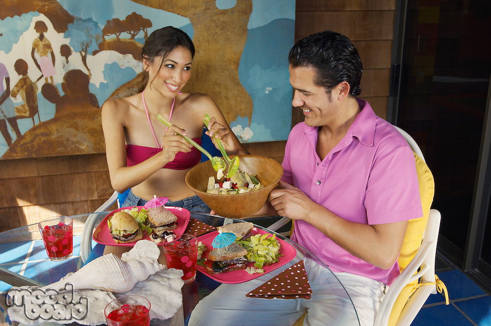 Couple eating meal at outdoor table