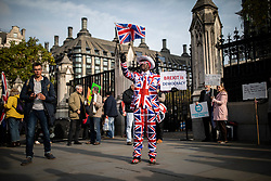 © Licensed to London News Pictures. 31/10/2019. London, UK. A Brexit supporter dressed in a Union Jack suit stands outside Parliament on 31 October 2019, the previous deadline for Brexit. MPs have voted for a December general election in order to break the deadlock in parliament over Brexit. Photo credit: Rob Pinney/LNP