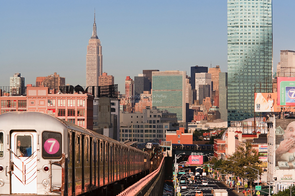 Subway train leaving Lowry Station, Sunnyside, Queens, New York with Empire State and United Nations Buildings in distance.