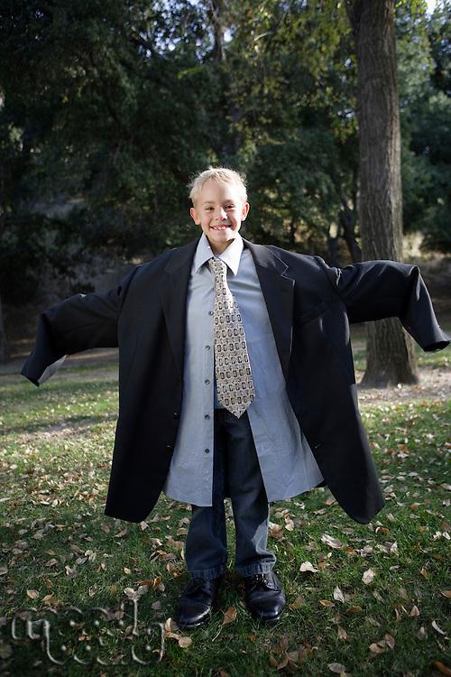 Boy (10-12) wearing oversized suit