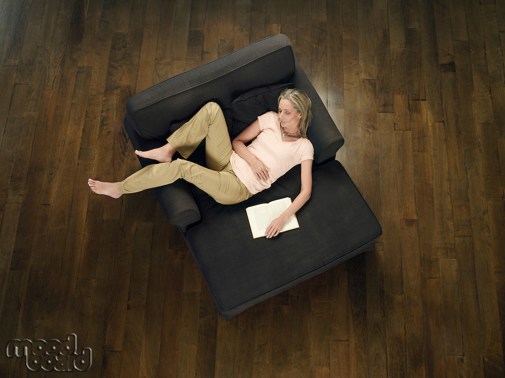 Mid adult woman sleeping on sofa holding book view from above