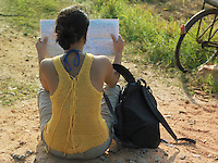 Young woman sitting on dirt road reading mapback view