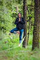 A woman balancing on a slack line in a yoga pose in a forest.