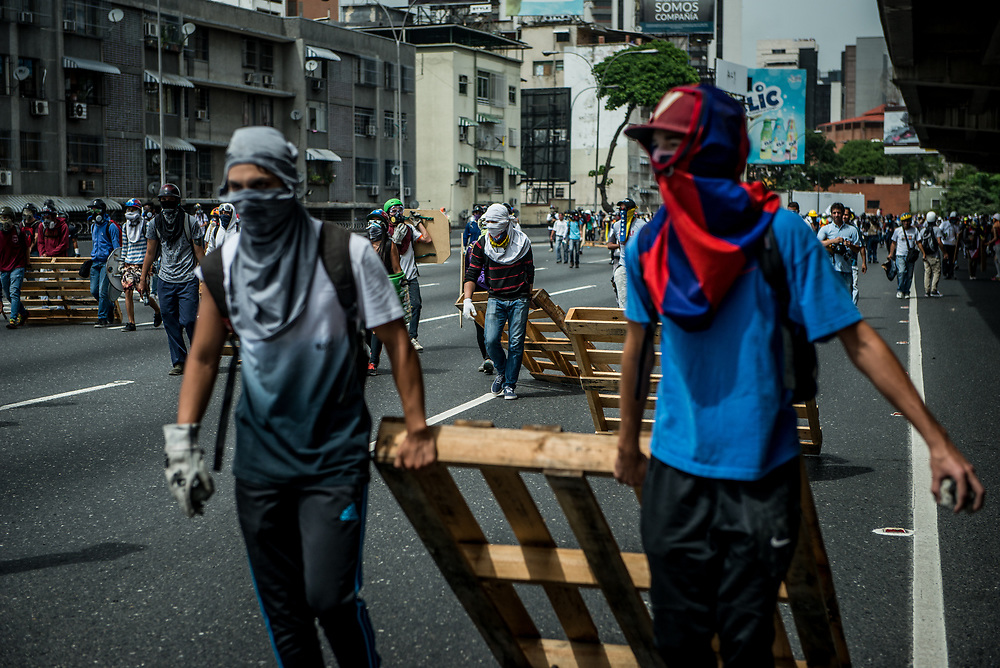 CARACAS, VENEZUELA - MAY 22, 2017:  Anti-government protesters drag pallets along the Francisco Fajardo highway in effort to build a road and and prevent police and soldiers from retaking control of the highway.  The streets of Caracas and other cities across Venezuela have been filled with tens of thousands of demonstrators for nearly 100 days of massive protests, held since April 1st. Protesters are enraged at the government for becoming an increasingly repressive, authoritarian regime that has delayed elections, used armed government loyalist to threaten dissidents, called for the Constitution to be re-written to favor them, jailed and tortured protesters and members of the political opposition, and whose corruption and failed economic policy has caused the current economic crisis that has led to widespread food and medicine shortages across the country.  Independent local media report nearly 100 people have been killed during protests and protest-related riots and looting.  The government currently only officially reports 75 deaths.  Over 2,000 people have been injured, and over 3,000 protesters have been detained by authorities.  PHOTO: Meridith Kohut