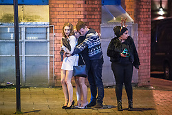 "© Licensed to London News Pictures . 16/12/2017. Manchester, UK. Three people huddle together for warmth as they wait at Deansgate Locks . Revellers out in Manchester City Centre overnight during "" Mad Friday "" , named for historically being one of the busiest nights of the year for the emergency services in the UK . Photo credit: Joel Goodman/LNP"