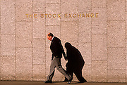 A middle-aged man walks beneath the sign of the London Stock Exchange at their old premises known as the Tower.  The gent looks hunched as if with all the troubles of the world on his shoulders, a pessimistic view on the world. He makes a sorrowful figure with such a strong presence against the wall shadow. Three years after the so-called Big Bang in 1986, this location at the old Stock Exchange Tower became redundant with the advent of the Big Bang, which deregulated many of the Stock Exchange's activities as it enabled an increased use of computerised systems that allowed dealing rooms to take precedence over face to face trading. Thus, in 2004, the House moved to a brand new headquarters in Paternoster Square, close to St Paul's Cathedral.
