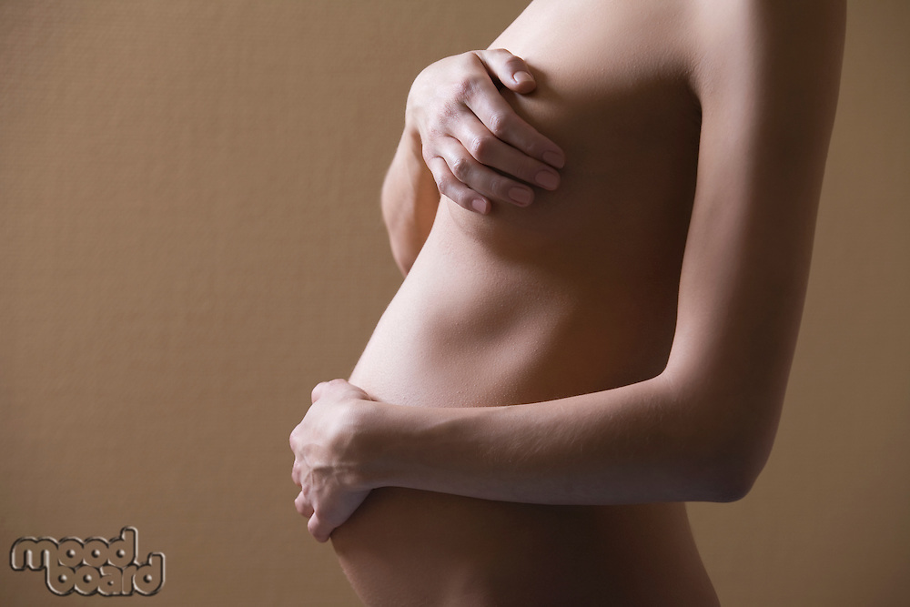 Pregnant woman stands with hand covering naked breast and stomach