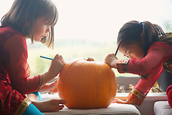 Young Girls Making a Pumpkin Lantern