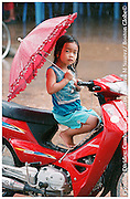 Siem Rap, Cambodia 031204   A young girls tries to stay dry under a downpour by climbing on a motorcycle and deploying an umbrella. (Essdras M Suarez/ Globe Staff)