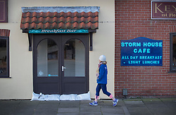 © Licensed to London News Pictures. 14/01/2017. Great Yarmouth, UK. A woman walks past the still sandbagged  Stormhouse Cafe in Gorleston-on-Sea. Hundreds of people are returning to their homes after flood warnings. A change in the wind direction stopped any major flooding to properties on the east coast of England.  Photo credit: Peter Macdiarmid/LNP
