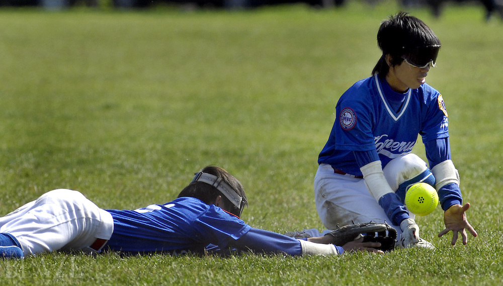 Wen-Shen Chiu, left, and Chun-Min Chen of Taiwan Homerun field a ball hit by the West Coast Dawgs  at the 2006 World Series of Beep Baseball in Strongsville, Ohio..Photo by Ken Blaze