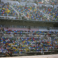 Rain falls as fans watch the driver introductions prior to the 57th Annual NASCAR Coke Zero 400 stock car race at Daytona International Speedway on Sunday, July 5, 2015 in Daytona Beach, Florida.  (AP Photo/Alex Menendez)