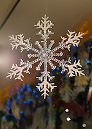 Huntington, New York, USA. February 20, 2014. A large plastic snowflake hangs from the ceiling at the Jingle Boom Holiday Bash, which has windows decorated by artists, at the Main Street Gallery of Huntington Arts Council.