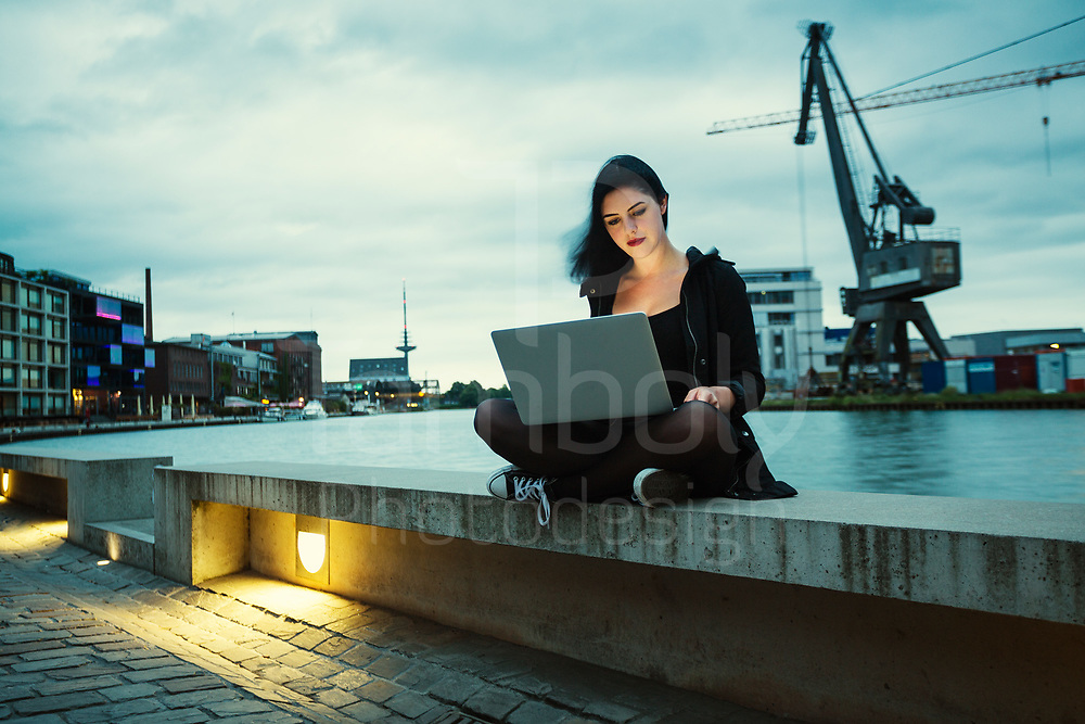 young girl in muenster on the harbour with laptop