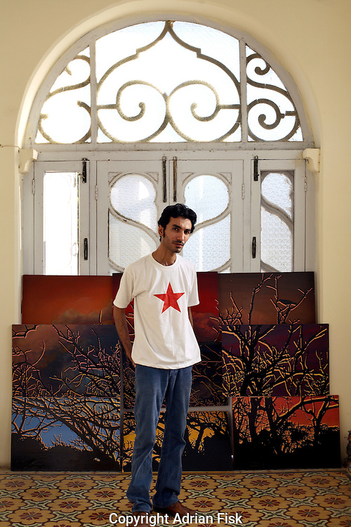 Asim Butt stands in his studio in Bhopal House in karachi. The painting behind titled 'View from Bhopal House' he had recently sold. The proceeds of which he was donating to the Karachi city district government so they could instal dustbins around the city..