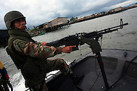 A member of the Colombian Navy keeps watch during a patrol of the waters along the coast that are used to ship drugs in Buenaventura, on the Pacific Coast of Colombia, on Monday, May 14, 2007. Buenaventura is in the midst of a spree of violence over control of drug shipments from the poor barrios in the city. Many of the neighborhoods have a strong presence of FARC militias that control most of the drug trade in the city. (Photo/Scott Dalton)