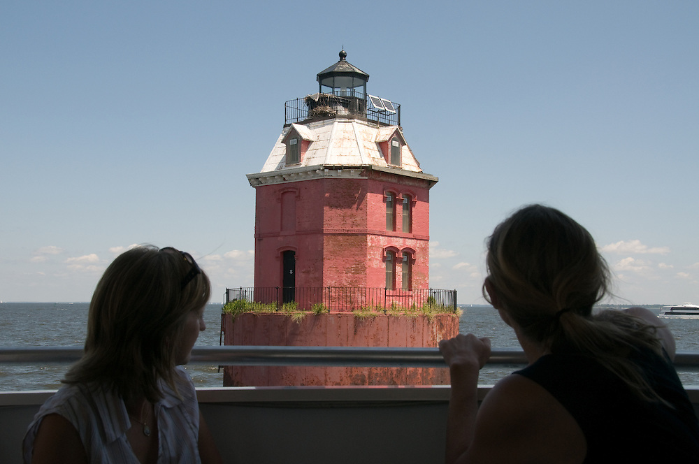 Women overlooking a lighthouse from ferry ride