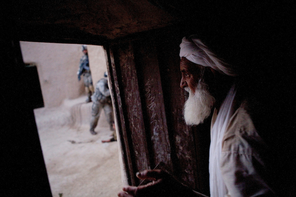An Afghan watches as members of the 82nd Airborne's 1/508 Parachute Infantry Regiment search his home after staging a nighttime air assault into Sangin, Helmand province, the largest air assault in Afghanistan since the beginning of the war, on Thursday, April 5, 2007.