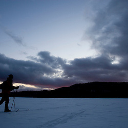 Cross-country skier at night on New Hampshire's Third Connecticut Lake.  February.