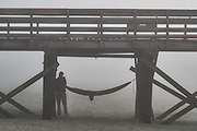 A man arranges his hammock under the Isle of Palms pier in a thick blanket of fog beach near Charleston, South Carolina.