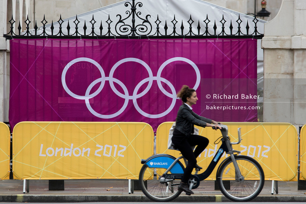 On a Barclays Bank-sponsored 'Boris' bike, a woman cyclist pedals past IOC's Olympic logo brand of rings on a banner at Horse Guards in Whitehall during the London 2012 Olympics. Wrought iron railings are seen behind the banner at the sports venue hosting the volleyball in the centre of Westminster where governmental offices are located.