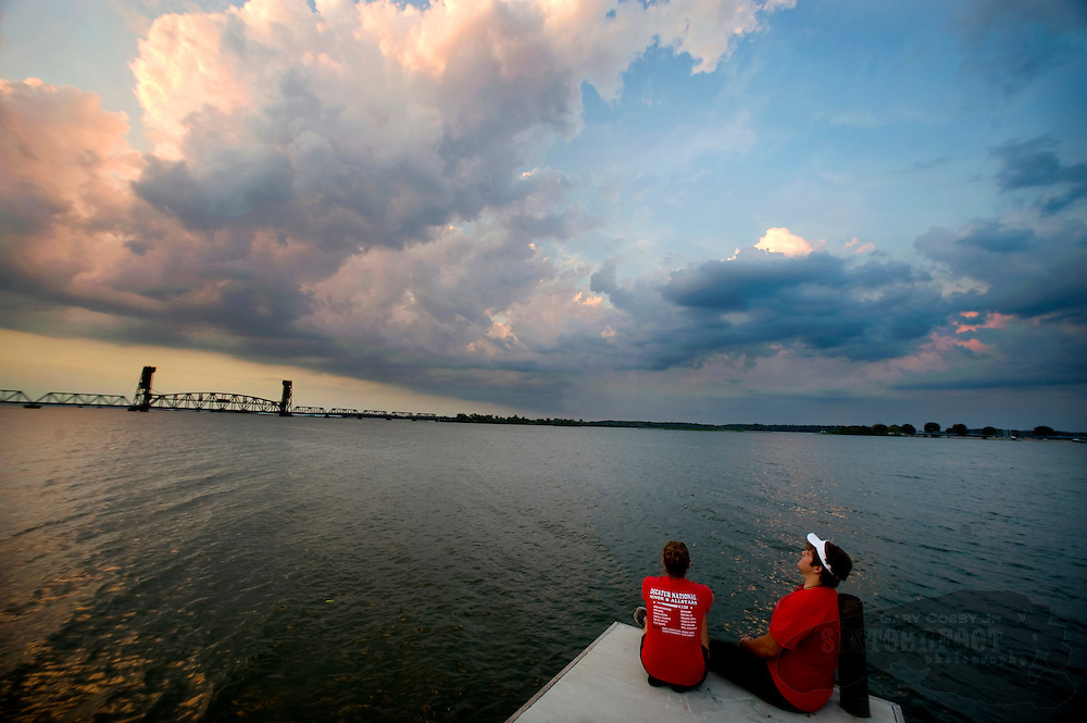 Photo by Gary Cosby Jr.  Heather Speegle and Jake Berry sit on a dock along the Decatur river front and watch the clouds roll by late Monday evening.  Speegle is from Hartselle and attends UAH and Berry is a student at Decatur High School.
