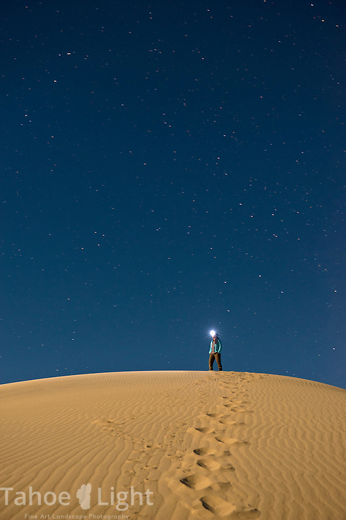 Woman on top of Eureka Dunes sand dunes in Death Valley National Park at night.