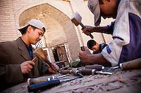 Muslim students of Madrassa add a special embellishment to a door in Khiva, Uzbekistan.