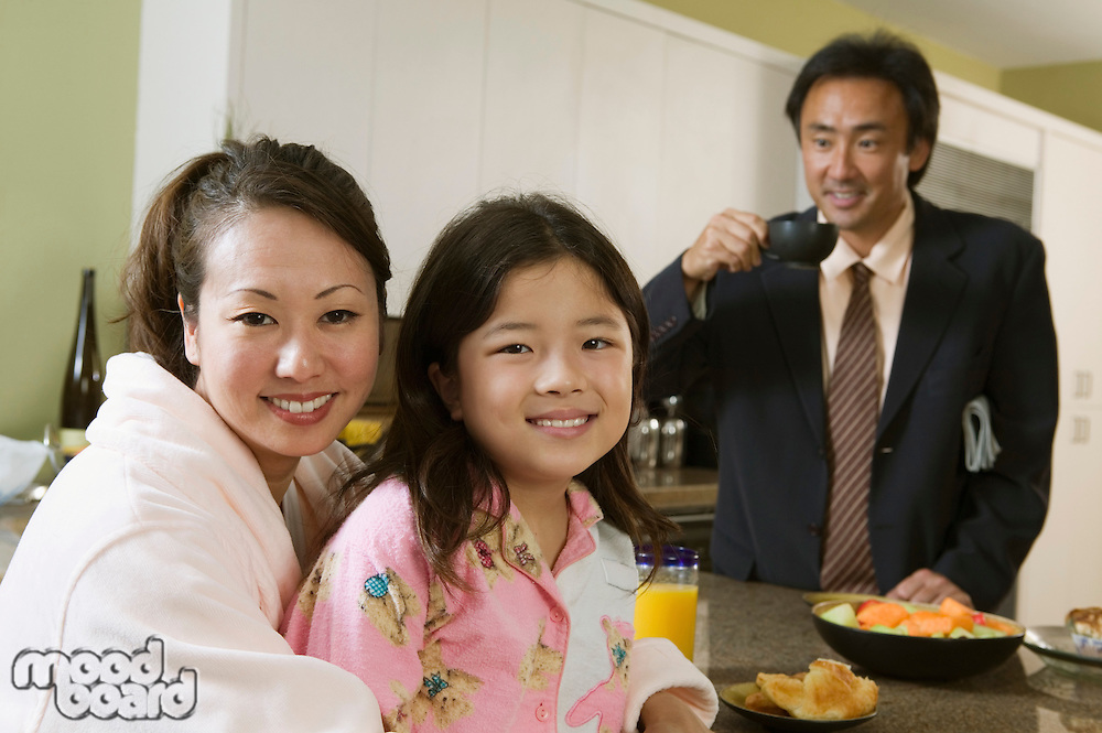 Mother and daughter at breakfast table father ready for work portrait