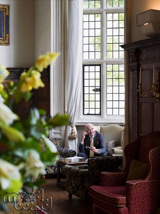 Senior man sitting in interior with antique furniture using mobile phone