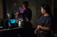 Sara and Estela Perez make coffee in the evening on a stove outside of their home. Before bedtime the family will gather and watch television inside their one room home.