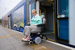 Woman wheelchair user getting off the tram,,