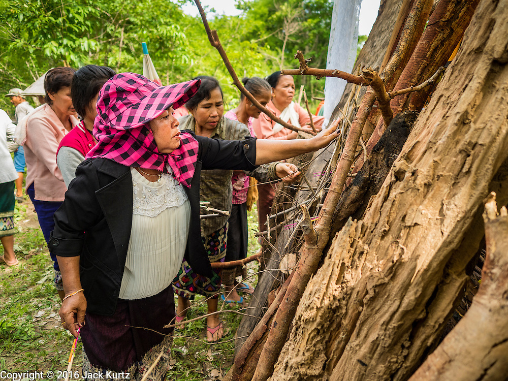 20 JUNE 2016 - DON KHONE, CHAMPASAK, LAOS: A mourner puts kindling next to the coffin of a man about to be cremated near Don Khone village on Don Khone Island. Don Khone Island, one of the larger islands in the 4,000 Islands chain on the Mekong River in southern Laos. The island has become a backpacker hot spot, there are lots of guest houses and small restaurants on the north end of the island. In the southern Lao funeral tradition, the deceased is cremated at the place of his choosing, usually a place he (or she) was especially fond of. In this case, the man chose to be cremated in a small clearing in the jungle a few kilometers from his home.     PHOTO BY JACK KURTZ