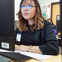 Tohatchi High School senior Louvaninna Tsosie, 17, at the computer, begins to set up her work station for the Business Professionals of America test in Albuquerque Feb. 14, 2019.