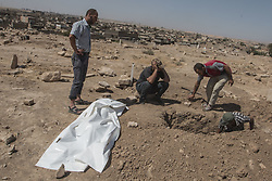 August 6, 2017 - Mosul, Ninevah, Iraq - Two men bury thier 9 year old brother killed in airstirke in Mosul's Shifa nieghborhood.  The boy's body was recovered with the help of the Civil Defense Force, who daily go on missions to recover the bodies those killed during the Iraqi military's 9 month long battle to retake the city from ISIS. (Credit Image: © Adryel Talamantes via ZUMA Wire)