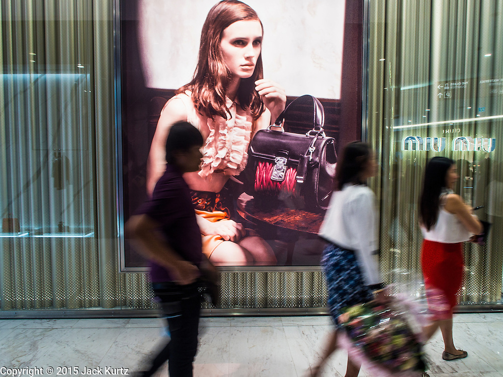 "27 MARCH 2015 - BANGKOK, THAILAND: Shoppers walk past Miu Miu, a high end women's fashions and accessory store in the ""EmQuartier,"" a new mall in Bangkok. ""EmQuartier"" is across Sukhumvit Rd from Emporium. Both malls have the same corporate owner, The Mall Group, which reportedly spent 20Billion Thai Baht (about $600 million US) on the new mall and renovating the existing Emporium. EmQuartier and Emporium have about 450,000 square meters of retail, several hotels, numerous restaurants, movie theaters and the largest man made waterfall in Southeast Asia. EmQuartier celebrated its grand opening Friday, March 27.    PHOTO BY JACK KURTZ"