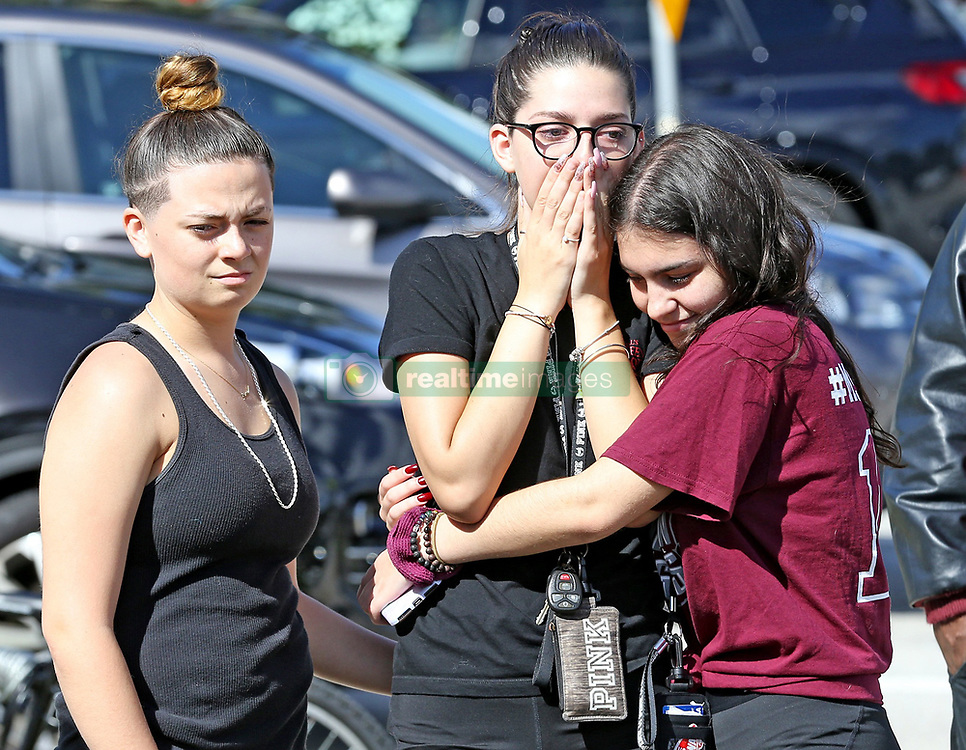 At 2:21 p.m., Riley Roland stands next to Bella Montecino as she hugs Makenzie Henser Thursday, February 14, 2019, at Marjory Stoneman Douglas High School in Parkland, FL, USA, as they have a moment of silence to mark the time when 17 students and teachers were killed in a mass shooting on Valentine's Day last year. Photo by Charles Trainor Jr./Miami Herald/TNS/ABACAPRESS.COM