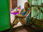 25 FEBRUARY 2015 - PHNOM PENH, CAMBODIA: A woman sits in the doorway of her apartment in the White Building in Phnom Penh. The White Building, the first modern apartment building in Phnom Penh, originally had 468 apartments, and was opened the early 1960s. The project was overseen by Vann Molyvann, the first Cambodian architect educated in France. The building was abandoned during the Khmer Rouge occupation. After the Khmer Rouge were expelled from Phnom Penh in 1979, artists and dancers moved into the White Building. Now about 2,500 people, mostly urban and working poor, live in the building. Ownership of the building is in dispute. No single entity owns the building, some units are owned by their occupants, others units are owned by companies who lease out apartments. Many of the original apartments have been subdivided since the building opened and serve as homes to two or three families. The building has not been renovated since the early 1970s and is in disrepair. Phnom Penh officials have tried to evict the tenants and demolish the building but residents refuse to move out.    PHOTO BY JACK KURTZ