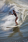 A women surfer takes advantage of the ocean swell generated by a passing hurricane along the South Carolina coast in Folly Beach, SC