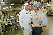 Bob Simpson, President and COO of Jelly Belly talks with an employee on the factory floor in Fairfield, Calif..
