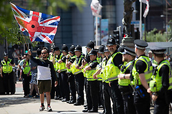 """© Licensed to London News Pictures . 07/07/2018 . Leeds , UK . An anti-Islam demonstration by supporters of jailed EDL founder Tommy Robinson , including those from the """" Yorkshire Patriots """" and """" First for Britain """" , in Leeds City Centre , opposed by anti-fascists . Robinson ( real name Stephen Yaxley-Lennon ) was convicted of Contempt of Court in May 2018 after committing a second offence , whilst serving a suspended sentence for the same crime . Photo credit : Joel Goodman/LNP"""