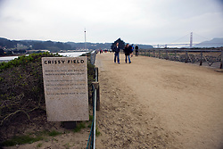 People walk along the Bay Trail at Crissy Field with the Golden Gate Bridge in the background, Golden Gate National Recreation Area, San Francisco, California.