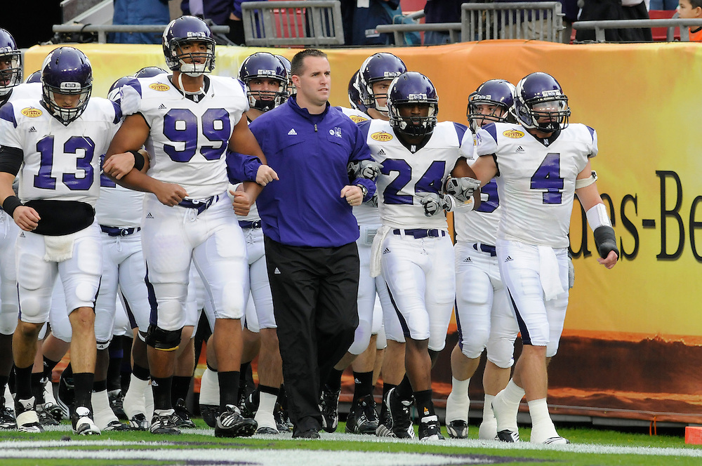 January 1, 2010: Head coach Pat Fitzgerald (center) of the Northwestern Wildcats with Mike Kafka (13), Corey Wootton (99), Sherrick McManis (24) and Brendan Smith (4) take the field before the NCAA football game between the Northwestern Wildcats and the Auburn Tigers in the Outback Bowl.