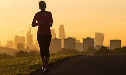 Primrose Hill, London, October 4th 2016. A woman goes for an early morning run as dawn breaks across London, throwing the city's skyline into silhouette.