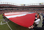 A large American flag is displayed on the field as part of pregame festivities before the Denver Broncos NFL week 19 AFC Divisional Playoff football game against the Indianapolis Colts on Sunday, Jan. 11, 2015 in Denver. The Colts won the game 24-13. ©Paul Anthony Spinelli