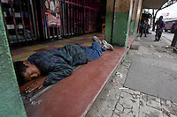A child finds slight refuge on the stoop of a store as he sleeps in Guatemala City's Zone 8.